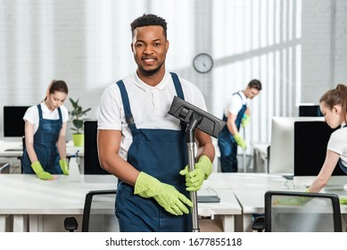 smiling african american cleaner holding vacuum cleaner brush near team of multicultural colleagues