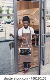 smiling african american coffee shop owner with open sign
