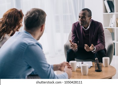 Smiling african american counselor talking to young couple in office