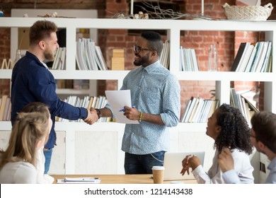 Smiling African American employer handshake millennial worker greeting with good work result during meeting, happy black CEO shake hand of Caucasian employee congratulating with success at briefing