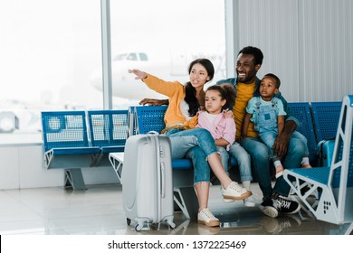 smiling african american family with baggage and kids sitting in airport while mother pointing with finger away