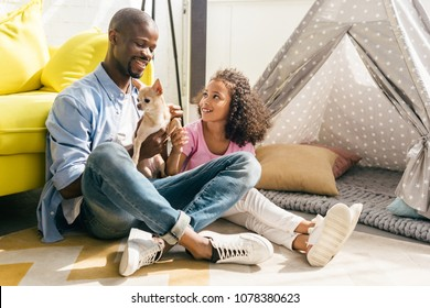 smiling african american family with chihuahua dog sitting on floor together at home