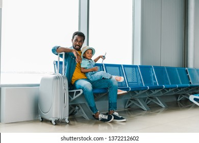 smiling african american father sitting with son and baggage in airport