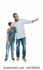 smiling african american father and son standing together and pointing away with finger isolated on white