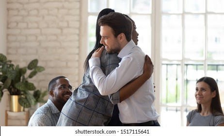 Smiling african american female employee hugging embracing happy coworker, giving support at group therapy session. Mixed race friendly teammates overcoming problems together, team building activity.