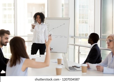 Smiling African American female mentor or coach training employees in office, interacting with workers asking questions, black woman give flipchart presentation for company interns teaching business