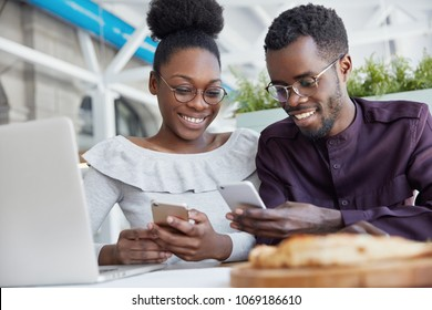 Smiling African American friends meet together at cafe, use modern technologies for entertainment. Dark skinned delighted young female and male hold smart phones, download new applications or files