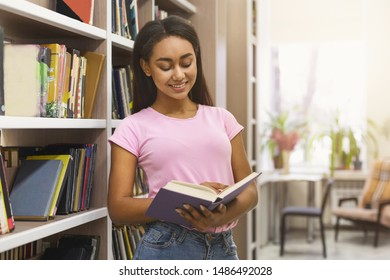 Smiling african american girl student reading book between bookshelves in campus library, empty space