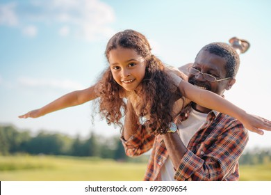 smiling african american grandfather playing with granddaughter at sunny day