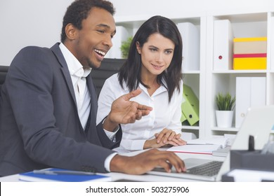 Smiling African American guy is showing his colleague the results of his work. She seems impressed and interested. Concept of understanding with coworkers