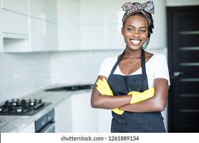 smiling african american housewife in apron with arms crossed
