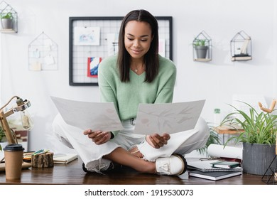 smiling african american interior designer sitting on desk with crossed legs and looking at paintings