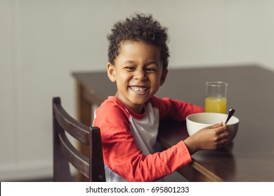 smiling african american kid eating healthy breakfast