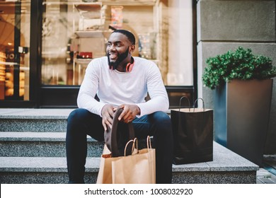 Smiling african american male customer in trendy wear sitting on stairs of store with bags with copy space for label, cheerful dark skinned hipster guy recreating after shopping and buying purchases