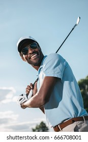 Smiling african american man in cap and sunglasses holding club and playing golf