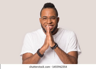 Smiling African American man in glasses join hands in anticipation, expectation, funny young male looking at camera, waiting anything good, making wish, desire, isolated on studio background
