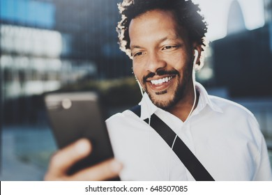 Smiling African American man in headphone making video call via mobile phone in hand.Concept of guy using Internet-enabled electronic device outdoor.Blurred background