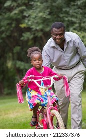 Smiling African American Man Helping Little Girl Biking Outdoor