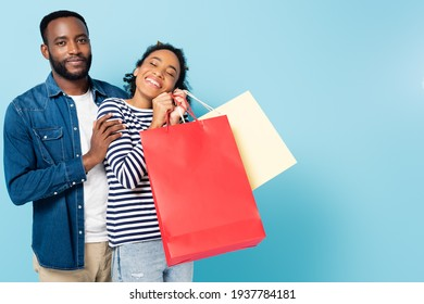 smiling african american man looking at camera near happy wife with shopping bags on blue
