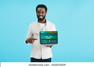 smiling african american man pointing at laptop with sports bet website isolated on blue