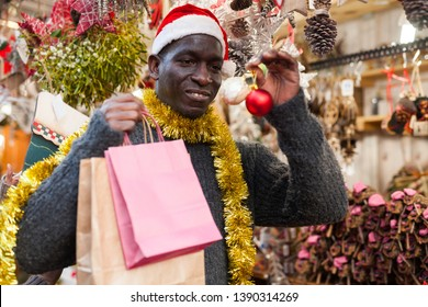 2c113e3067481 Smiling African American man in Santa hat selecting festive home decoration  at outdoor Christmas fair