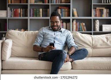 Smiling african American man sit relax on comfortable couch at home using modern cellphone, happy biracial millennial male rest on sofa in living room texting messaging on smartphone gadget