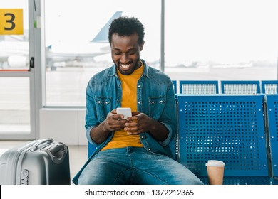 smiling african american man sitting in departure lounge and using smartphone