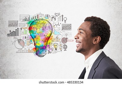 Smiling African American man standing near concrete wall with colorful light bulb and startup sketches. Concept of bright idea.