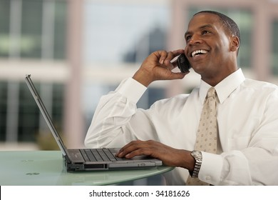 Smiling African American man talking on cell phone at desk with computer