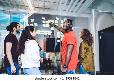 Smiling African American man with young multiethnic group mates standing near glass wall with bright sticky notes while brainstorming on plan