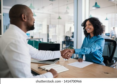 Smiling African American manager sitting at his desk in an office shaking hands with a job applicant after an interview