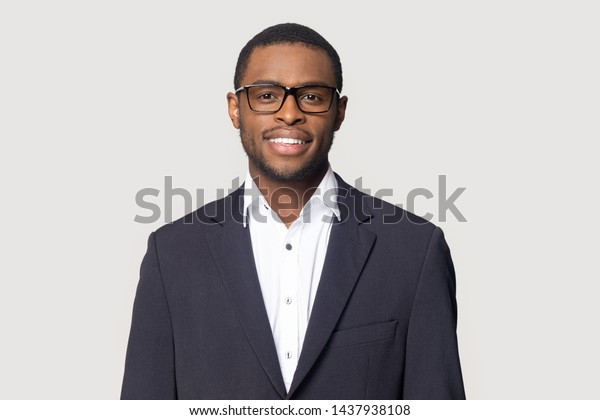 Smiling african American millennial businessman in glasses isolated on grey studio background posing, satisfied successful black male in formal suit wearing spectacles look at camera laughing