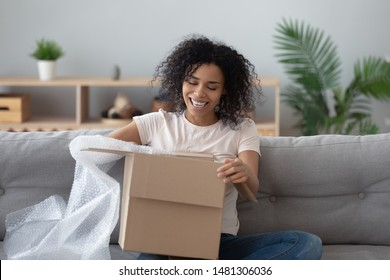 Smiling african American millennial girl sit on sofa at home open cardboard delivery package shopping online, excited black young woman unpack unwrap parcel buying good via internet or web