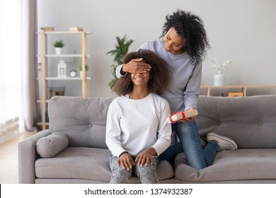 Smiling African American mother closing eyes of happy teen daughter, preparing surprise for birthday, mum holding gift box, sitting together on couch in living room, family celebration at home