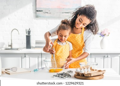 smiling african american mother helping daughter mixing eggs for dough in kitchen