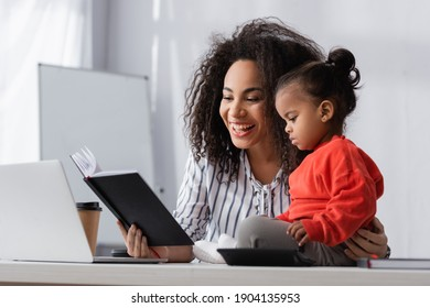 smiling african american mother looking at notebook near toddler daughter on desk