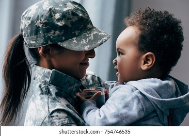 smiling african american mother in military uniform with her little son at home