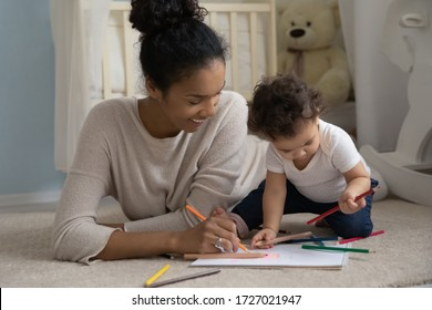 Smiling african American mother relax on floor at home drawing painting with small toddler baby, happy young biracial mom engaged in learning activity with little infant child, childcare concept
