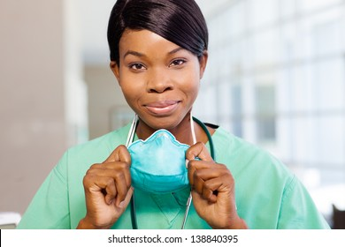 Smiling African American nurse at hospital work station lit brightly with phone and stethoscope.