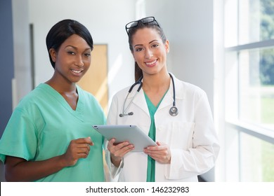 Smiling african american nurse in scrubs and caucasian doctor in scrubs and white lab coat holding a tablet computer in brightly lit  hospital halway.