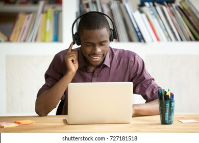 Smiling african american office worker in headphones looking at laptop screen. Young  casual businessman studying foreign language, communicating with clients through video conference application.
