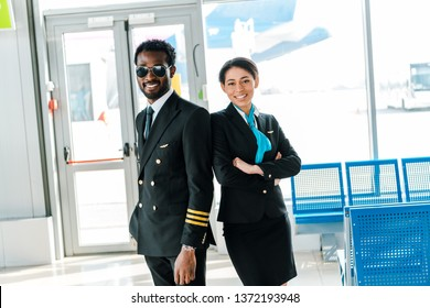 smiling african american pilot in sunglasses and stewardess with crossed arms standing together in airport