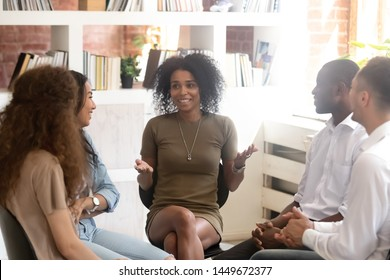 Smiling African American psychologist counselling, speaking with diverse people sitting in circle at group therapy session, business coach training staff, having fun, team building activity at work