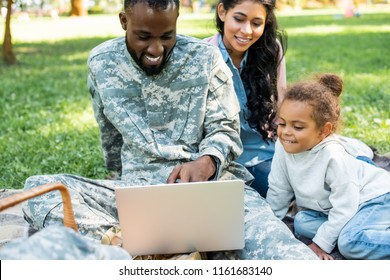 smiling african american soldier in military uniform using laptop with family in park
