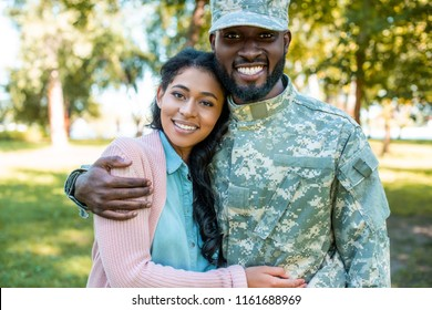smiling african american soldier in military uniform hugging girlfriend in park