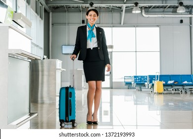 smiling african american stewardess standing with suitcase in airport
