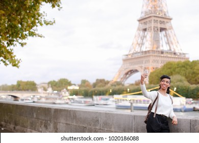 Smiling African American taking selfies on background of Eiffel Tower using silver smartphone. Young woman came to Paris for honeymoon. Black-haired woman with beautiful hair styling wearing