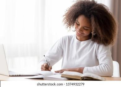 Smiling African American teen girl preparing school homework, using laptop, happy black schoolgirl, pupil doing tasks, writing essay, studying at home, making notes, writing, reading textbooks