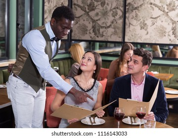 Smiling African American waiter taking order from couple, recommending dishes from restaurant menu