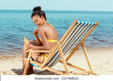 smiling african american woman applying sunscreen lotion on skin while sitting on deck chair on sandy beach